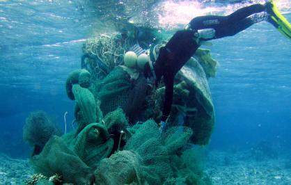 A marine debris removal diver conducts an assessment of a derelict net conglomerate at Midway Atoll, Northwestern Hawaiian Islands | Credit: JIMAR/NOAA PIFSC​