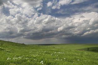rolling tallgrass prairie hills with moody sky